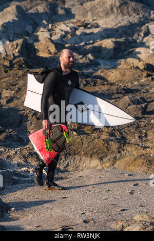 A disconsolate surfer carrying his snapped surfboard at North Fistral in Newquay Cornwall. - Stock Image