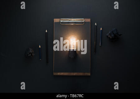 Light bulb shining in black flat lay with crumpled paper balls and a clipboard. The idea for engineering, building or construction concept with copy s - Stock Image