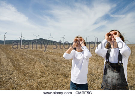 Children in a field with wind turbines - Stock Image