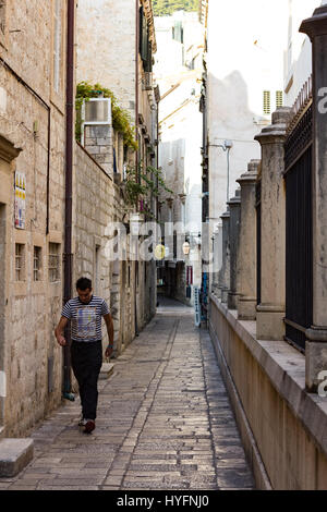 A man walks down a laneway in Old City, Dubrovnik - Stock Image