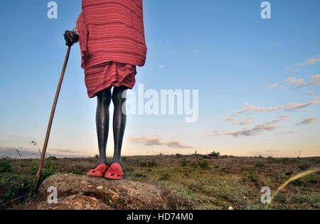 Maasai Warrior wearing traditional tribal clothing with Crocs. Blue sky in background. Kenya, Africa. - Stock Image