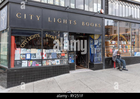 City Lights Books, shop front; homeless man resting by the entrance; San Francisco, California, USA - Stock Image