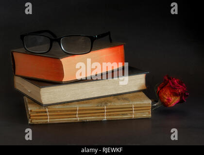 Reading glasses on top of three old books stacked on top of each other, against dark background- vintage reading concept - Stock Image