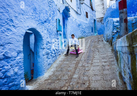 Chefchaouen, Morocco : A child plays at a steep lane in the blue-washed medina old town. - Stock Image