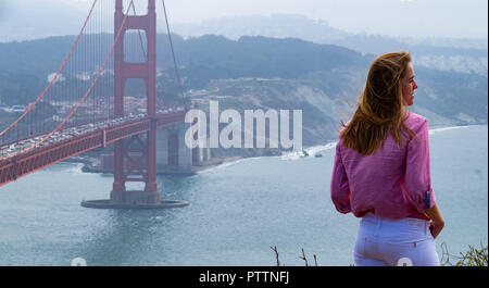 A female tourist standing at the cliff edge at Battery Spencer with the Golden Gate Bridge and San Francisco in the background with the San Francisco - Stock Image