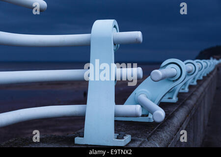 Blue railings on sea wall contrasting with dark sky. - Stock Image