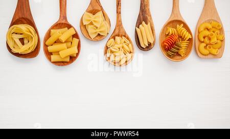 Italian foods concept and menu design. Various kind of Pasta Farfalle, Pasta A Riso, Orecchiette Pugliesi, Gnocco Sardo and Farfalle in wooden spoons  - Stock Image
