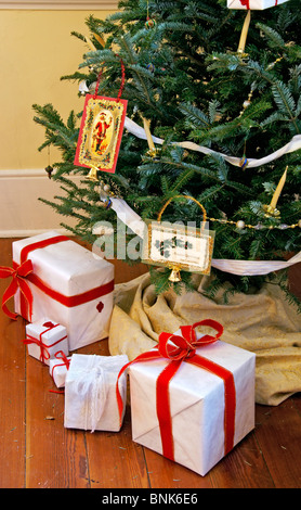 Wrapped gifts and presents under a decorated vintage Christmas tree - Stock Image