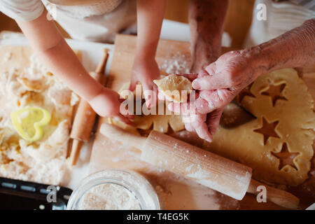A midsection of senior great grandmother with small toddler grandchild making cakes at home. - Stock Image