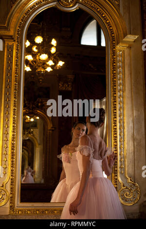 Beautiful ballerina in pink dress standing in front of the mirror on background of luxurious interior and her reflection. - Stock Image