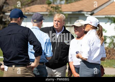 Panama City, Florida, USA. 15th Oct 2018. U.S President Donald Trump speaks to Florida Gov. Rick Scott during a tour of damage in the aftermath of Hurricane Michael October 15, 2018 in Lynn Haven, Florida. Standing with the president from left to right are: FEMA Administrator Brock Long, Florida Gov. Rick Scott, President Donald Trump, First Lady of Florida Ann Scott and First Lady Melania Trump. Credit: Planetpix/Alamy Live News - Stock Image