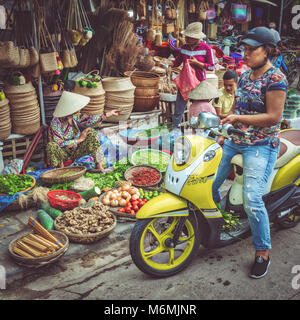 A lady on a moped stops next to a market trader to buy fruit and vegetables at Hoi An market - Stock Image