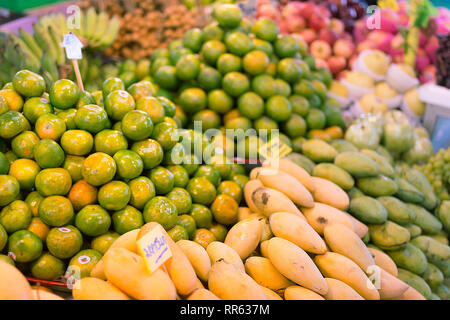 Fresh fruit, green oranges and yellow mangoes piled up on a market stall ready for sale. - Stock Image