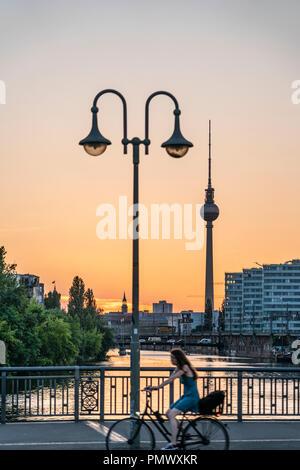 Schilling bridge , laterne,  Alex TV tower, river Spree, women on bicycle, Trias building,  sunset, Berlin - Stock Image
