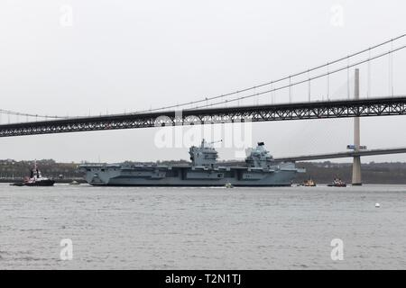 Queensferry, UK. 3rd Apr, 2019. UK, Europe. HMS Queen Elizabeth passes under the Forth Rail Bridge on a visit to Rosyth dry dock for scheduled maintenance checks prior to full operational deployment in 2020. Credit: Douglas Carr/Alamy Live News - Stock Image