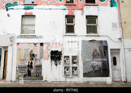 Tattered poster featuring Vinti Andrews model defaced and torn with graffiti on a wall at Turville Street Shoreditch East London E1  KATHY DEWITT - Stock Image