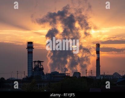 Sunrise over industrial factory with smoke rising between smokestacks. Behind smoke sun and orange clouds are visible - Stock Image