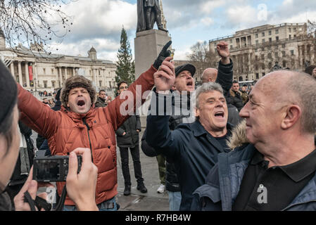 London, UK. 9th Dec, 2018. A small group of men shout insults at the marchers as the go thorugh Trafalgar Square. Police have to hold back antifascists who want to challenge them. The united counter demonstration by anti-fascists was in opposition to Tommy Robinson's fascist pro-Brexit march. Police had issued conditions on both events designed to keep the two groups well apart. Credit: Peter Marshall/Alamy Live News - Stock Image