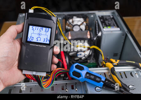 Hand tester of power supply unit. Open computer case. Digital measuring tool, connector, colorful cables. Pliers, screwdriver. PC hardware maintenance. - Stock Image