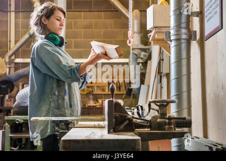 Young woman examining wood after cutting on machine in a workshop - Stock Image
