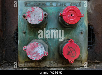 A standpipe connection with four pipes with red caps on the side of a building - Stock Image