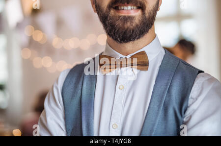 A midsection of man standing indoors in a room set for a party. - Stock Image
