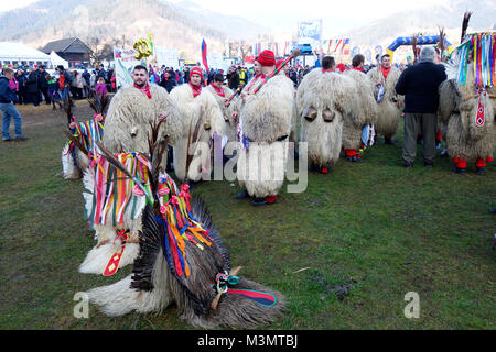 Slovenes 'Kurents' (kurentovanje) with face masques off have show during ski jumping competition in Ljubno - Stock Image