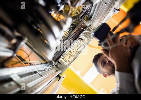 Technician using digital cable analyzer - Stock Image