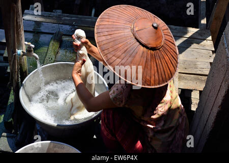 Woman washing the porous lotus fibers that are twisted and rolled together with water, spun,and then are washed - Stock Image