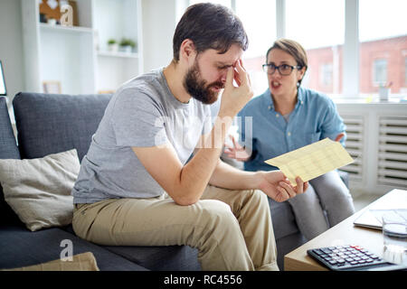 Desperate man holding letter with rejection of job application while his wife shouting at him - Stock Image