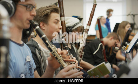 Selective focus view of serious teenage boy musician playing clarinet in band class - Stock Image