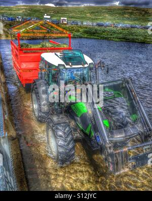 Tractor driving trough a river - Stock Image