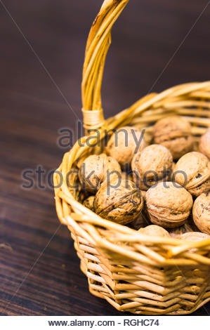 Whole walnuts with shell in a basket in soft focus - Stock Image