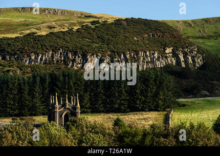 Border scenery in the Cheviot hills where Scotland joins England. Kirk Yetholm (end of the Pennine Way) church with quarry cliffs beyond. - Stock Image