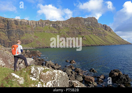 Mull, UK. 6th October 2018. Hill walker taking a breather to look at the wonderful coastline on this beautiful autumnal day, below Binnein Gorrie known locally as 'Gorrie's Leap' in a remote part of the Ross of Mull on the Hebridean island of Mull. Credit: PictureScotland/Alamy Live News - Stock Image