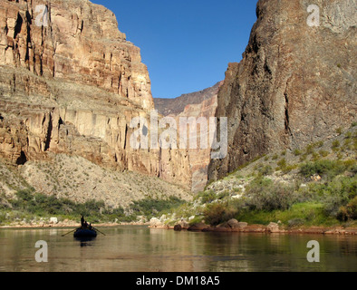 A single silhouetted raft drifting in the Grand Canyon. - Stock Image