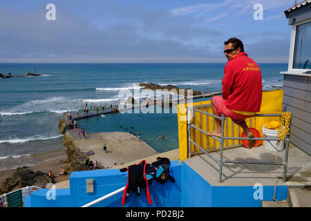 Bude, Cornwall, UK. RNLI lifeguard watches over swimmers enjoying the hot weather and water in one of Bude's semi-natural sea bathing pools - Stock Image