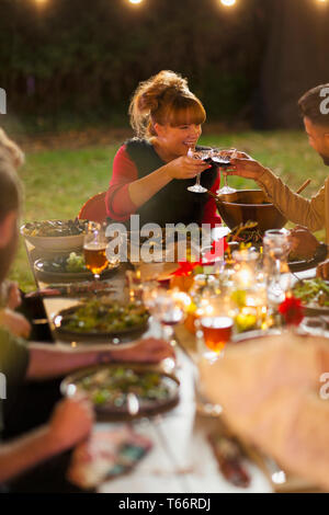 Happy friends toasting wine at dinner garden party - Stock Image