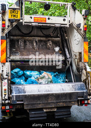Refuse Collection Truck or Bin Lorry London - London Rubbish Truck picking up waste in Central London. Refuse Sack Collection. Bin Bag Collection. - Stock Image