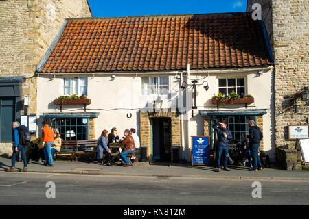 Tourists outside the Feathers Hotel in Bridge Street Helmsley North Yorkshire in Spring - Stock Image