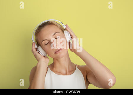 Portrait Handsome Young Woman Listening Headphones Music Player Blank Yellow Color Background.Pretty Girl Enjoy - Stock Image