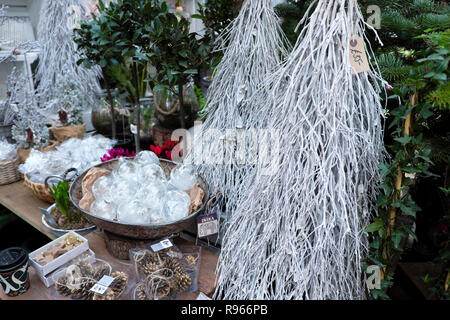 Christmas ornaments, white painted branches, glass baubles decorations for sale on a stall at Borough Market in South London England UK   KATHY DEWITT - Stock Image