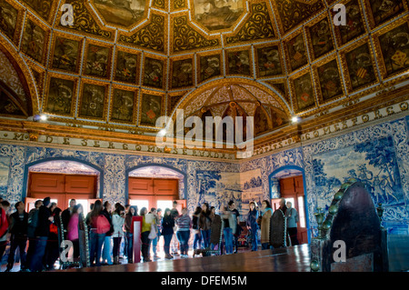 Visitors on a guided tour of the Palácio Nacional de Sintra, in Sintra, Portugal, gather in the Sala dos Brasões. - Stock Image