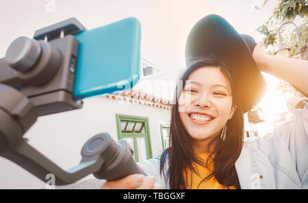 Asian woman making video with smartphone gimbal outdoor - Happy Asiatic girl having fun with new technology trends for social media - Stock Image