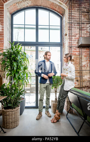 Business people having a conversation standing near the window in the beautiful loft interior - Stock Image