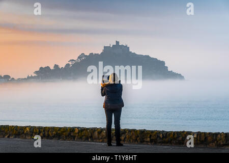 Marazion, Cornwall, UK. 29th Mar, 2019. UK Weather. As the sun rose in south west Cornwall, a mist formed on the sea shrouding the base of St Michaels Mount for another morning. This early morning commuter pulled over on the beach car park to get a picture of the misty Mount. Credit: Simon Maycock/Alamy Live News - Stock Image