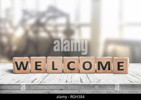 Welcome sign on a table in a lobby with a bright room in the background - Stock Image
