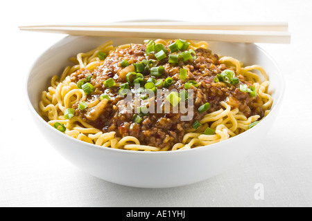 Tan Tan Noodles spicy oyster sauce meat beef chicken pork chinese food with green onion dish white plate delicious - Stock Image