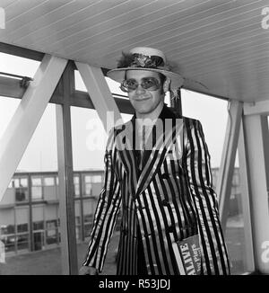 Pop star Elton John wearing a hat trimmed with flowers and feathers, on arrival at Heathrow Airport from Los Angeles, where he has been recording a new album. He has returned for a three-week stay and top of his list of his priorities is tomorrow's football match at Huddersfield where Elton will be shouting for his favourite team.. Watford. 30th August 1974. - Stock Image