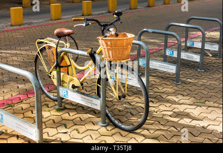 A woman's bike with an attached shopping basket in a bicycle parking space in Seville - Stock Image
